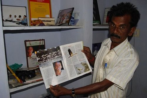 Bal Pandian proudly showing an article on his late wife, Vallithai Pandian