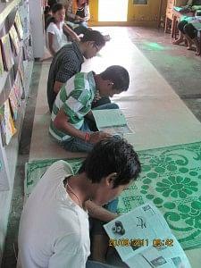 Children reading inside the Apne Library, Wakro