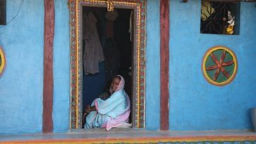 A tribal woman sitting at her door in Purushwadi