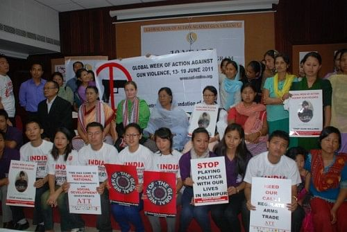 Women of the network at a meeting, holding photographs of the sons and husbands they have lost in gun violence in Manipur. (Credit: Azera Rahman\WFS)