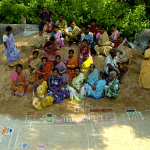 Local self help group members in Rangareddy Palayam village draw a local map on the main street, marking disaster-prone spots as part of a risk assessment exercise. Source: Trust.org