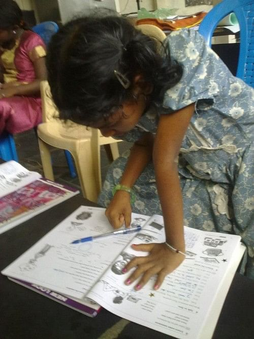 A girl from Childrens home centre in Injambakkam,Chennai, working on her workbook in MAD class