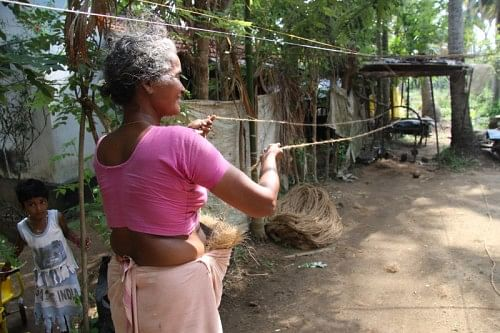 A lady spinning a coir yarn.