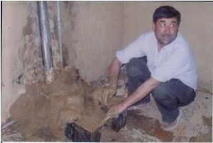 Mr Vidya Rattan Sharma making a cookstove in a kitchen