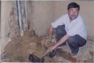 Mr Vidya Rattan Sharma making a cookstove in a kitchen