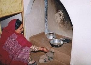 A lady using DEEP Chulha in her kitchen