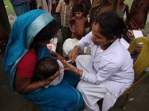 An ANM immunises a child in a health camp organised by the boat clinic in the Nalbari district of Assam.