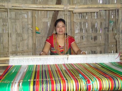 A Hajong woman weaving a beatiful multi-hued garment.