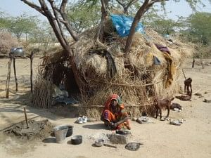 A Bagaria woman outside her hut of baked mud and thorny branches