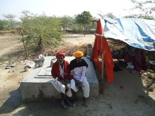 Bagariya men sitting outside their hut. Most of them own no more than a small parcel of land, compelling them to work as lowly-paid labourers or as guards in other people's fields.