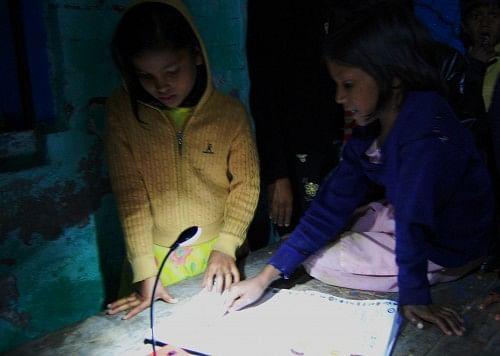 Girls studying using a solar light