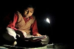 Boy studying with solar LED light provided by OCOL
