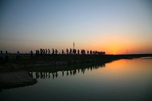 The reflection of sunset in one of the lakes, with students of AIM walking along the lake.