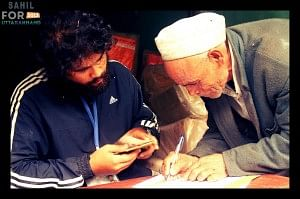 A volunteer gets a signature of the villager after he has collected the relief supplies