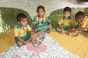 Happy children playing on the butterfly mosaic on the school floor