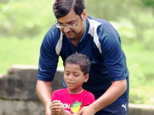 Founder, Akshai Abraham, teaching under hand to a beneficiary, during a volleyball session