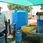 Alagesan with the barrel used to ferment cow dung