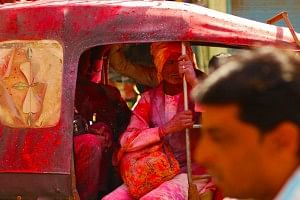 A three wheeled tuk-tuk (auto rickshaw) covered in red gulaal ferrying people within the city.