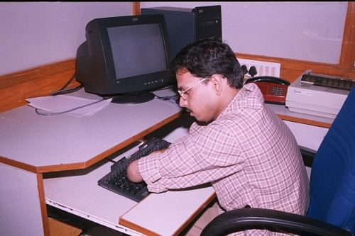 Raja at his desk at ONGC, where he can efficiently work on the computer as well