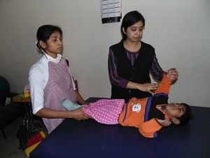Therapist checking a child at Bal Chetna-DCCW's respite Home and Day-care facility for mentally challenged children