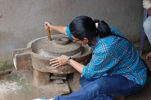 A city girl trying her hand at grinding rice
