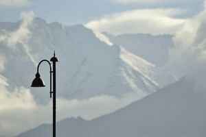 View of a streetlight against snowy mountains outside KBR Airport, Leh.