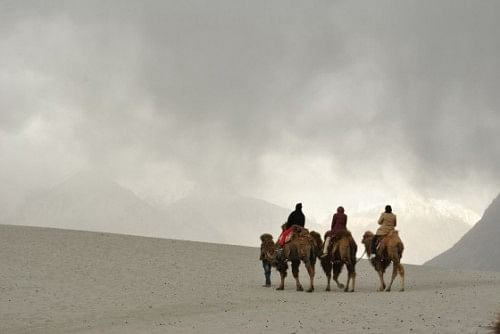 Riding double-humped camels on the sand dunes at Nubra Valley.
