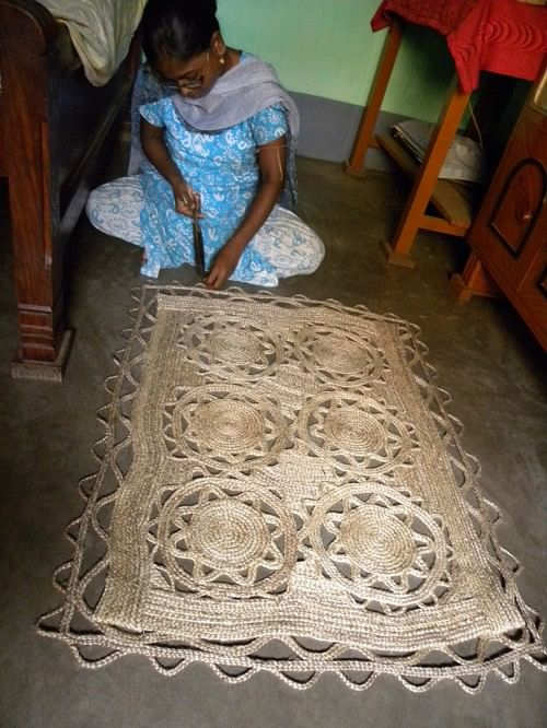 A young student creates a jute carpet.