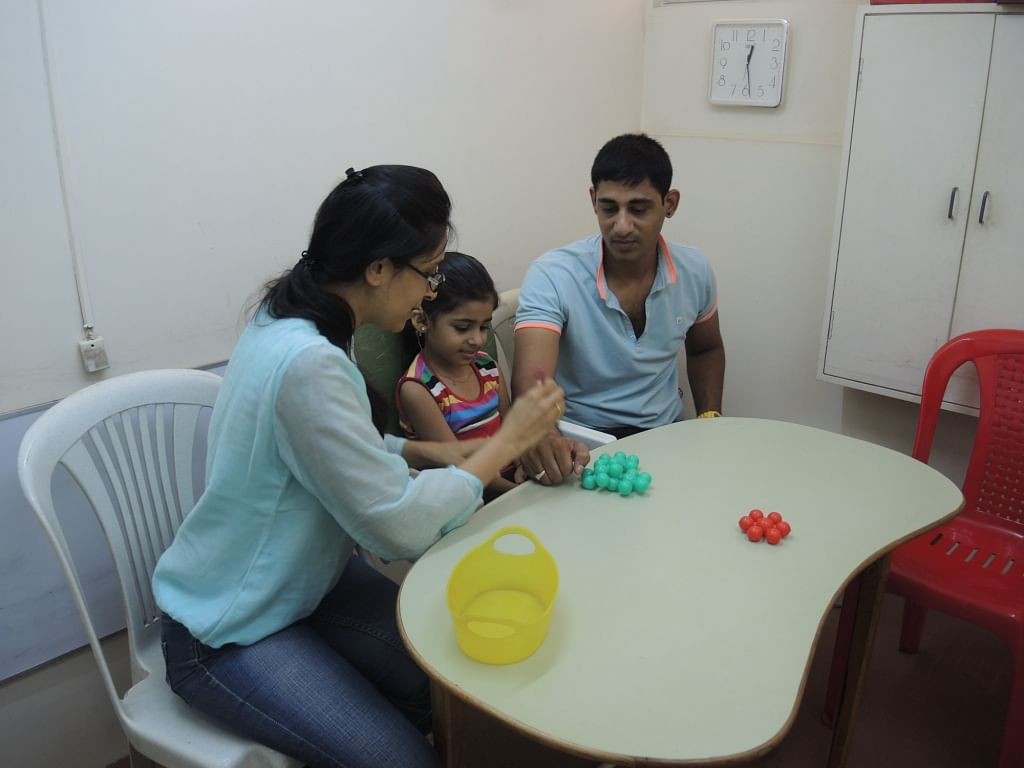 A teacher with the student and his father engages them in therapy sessions.