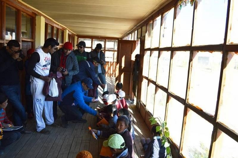 The team distributes stationary items to the local schools in the hills.