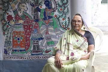 "This is Karpuri Devi, 86, younger sister-in-law of the renowned Madhubani artist, Mahasundari Devi, whose name is synonymous with this folk style. Sitting in the veranda of her single storey home, which she has painted with ornate patterns and figures in Madhubani, Karpuri reminisces about the days when she had first picked up the brush, ""Decades ago, women in the village were not allowed to step outside the confines of the home. We had to be very discreet about our work. Typically, we used twigs, brushes, matchsticks or nib-pens to make paintings with themes from the Ramayana or what we saw of daily life around us. For years, the wall was our canvas. Paper came much later."""