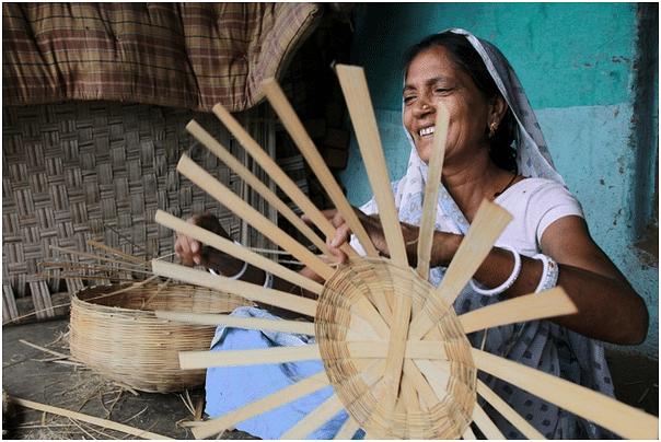 Mangudi, a Bhil artisan, sells baskets and brooms in the local market.