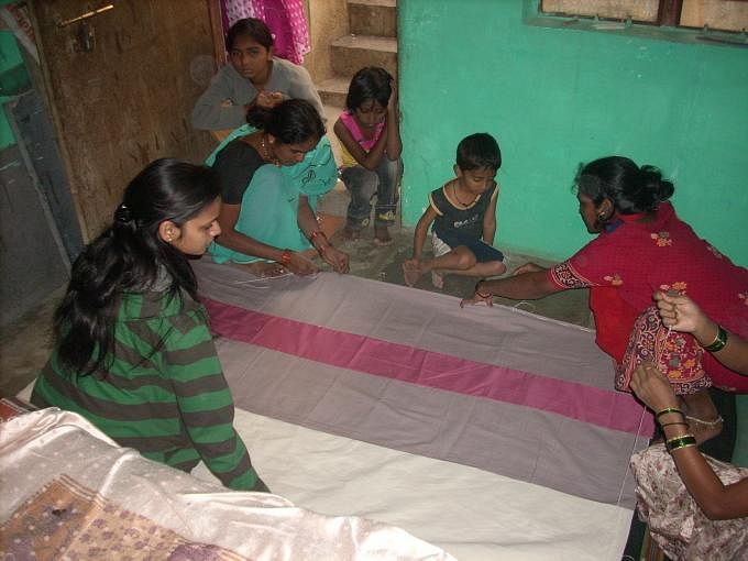 The women from slums make bags out of old saris to get some extra income.
