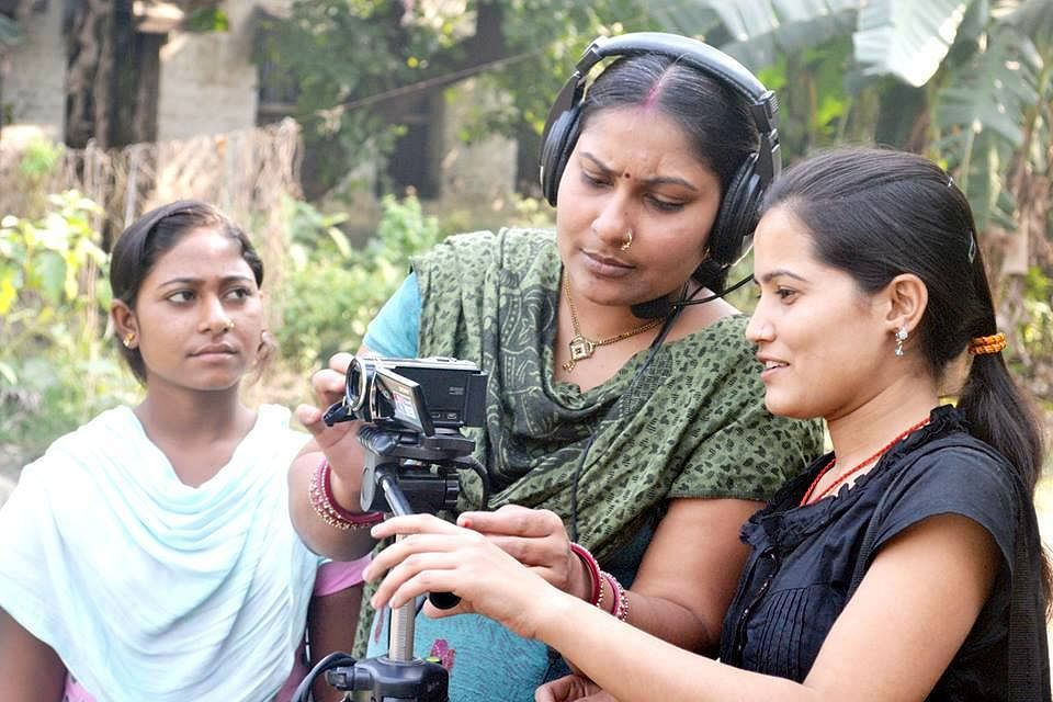 Fortnightly women reporters of Appan Samachar meet to decide on the topics to cover before different teams, comprising one reporter and another with a hand-held camera, pan out to different areas on a bicycle to interview villagers.