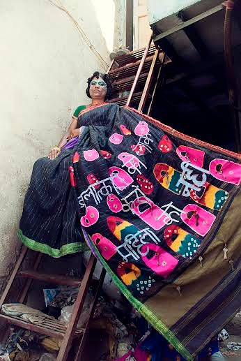 Dharavi resident, Rutha David, shows off the black silk sari designed by her that has a patchwork 'pallu' with the message: 'Balatkari ko lock karo, mahila ko nahin' (lock the rapist and not the victim). (Courtesy SNEHA)