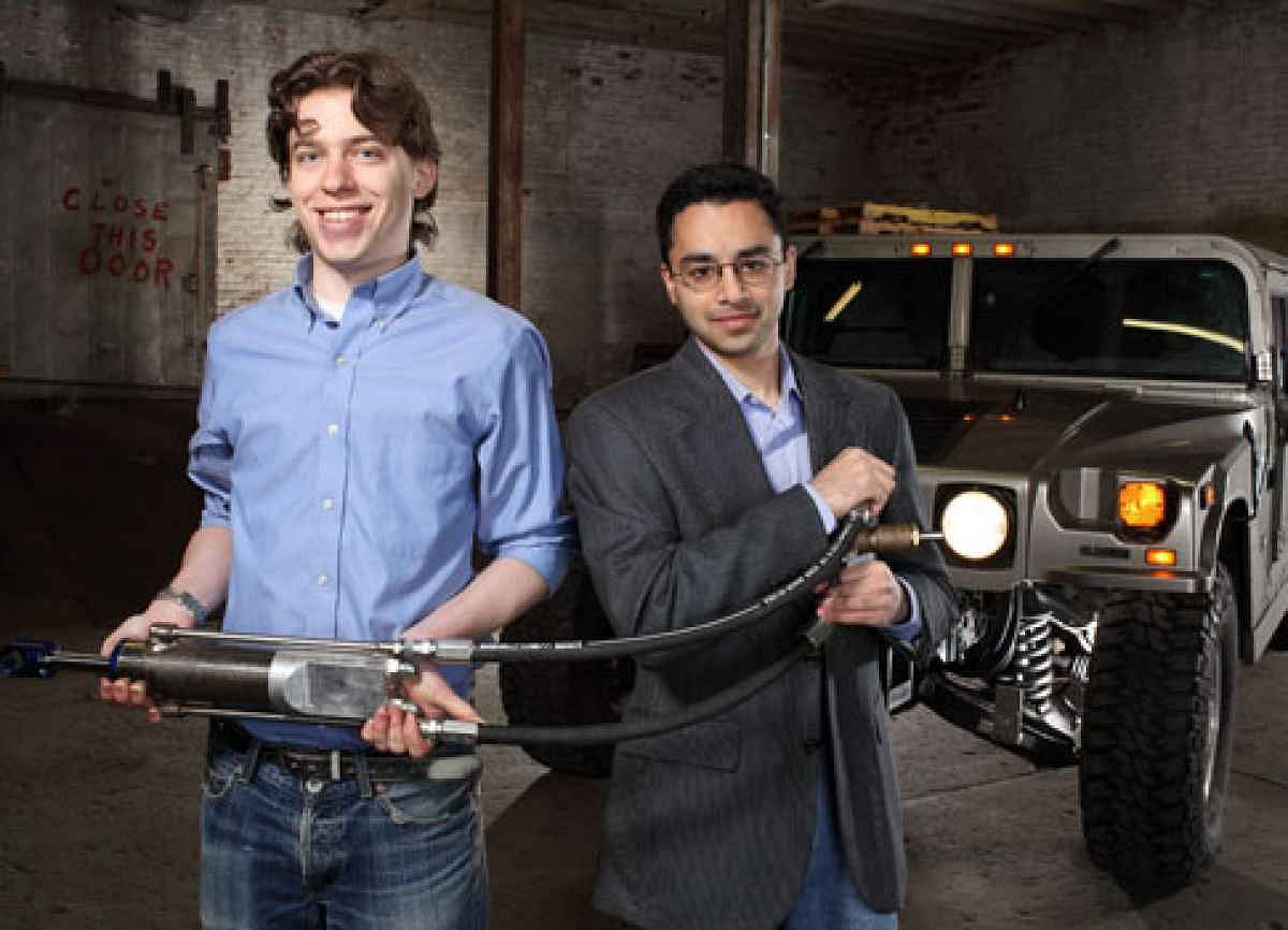 Power Players Zack Anderson (left) and Shakeel Avadhany (right), with a prototype power harvesting shock absorber, to be fitted to a Humvee vehicle. Photo credit – John B Carnett.