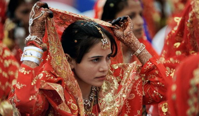 An Indian Muslim bride adjusts her veil as she waits for the start of a mass wedding in Ahmedabad on March 21, 2010. Some 201 Muslim couples participated in a mass wedding organised by The Gujarat Sarvajanik Welfare Trust. AFP PHOTO/ Sam PANTHAKY (Photo credit should read SAM PANTHAKY/AFP/Getty Images)