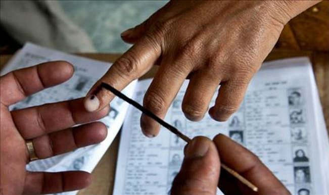 Polling Official applying a drop of Indelible Ink on the index finger of a voter.