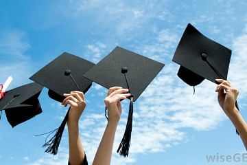 hands-holding-graduation-caps-in-air