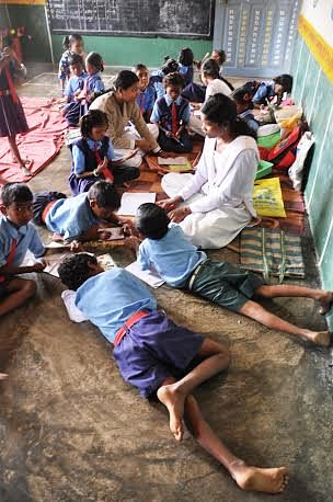 Instead of the customary chairs and tables, students and teachers at the Government Primary School in Motwada, sit together on the floor, interact with each other as equals and there is a concerted effort towards making lessons fun and informative for the young ones. (Credit: Purusottam Singh Thakur\WFS)