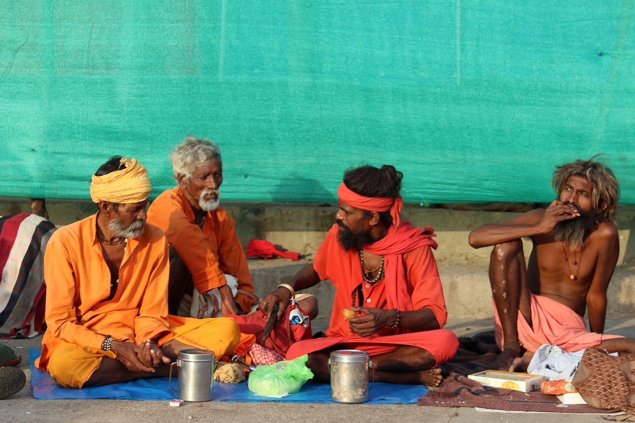 Sadhus line up at ghats for alms