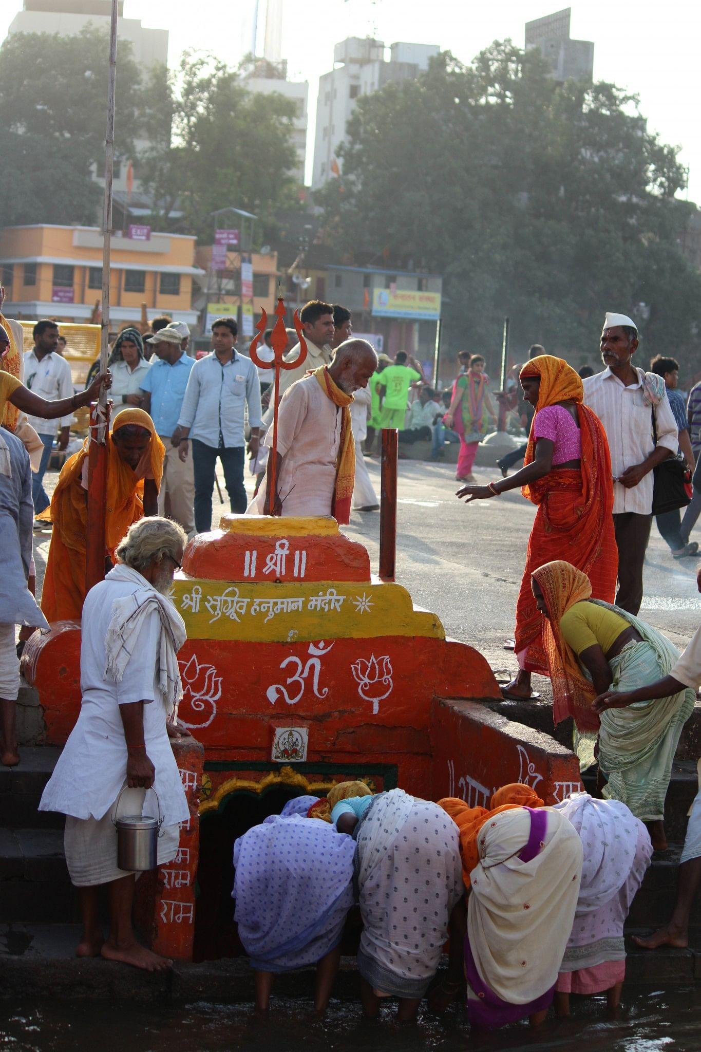 Pilgrims get down in water to pray at Hanuman temple
