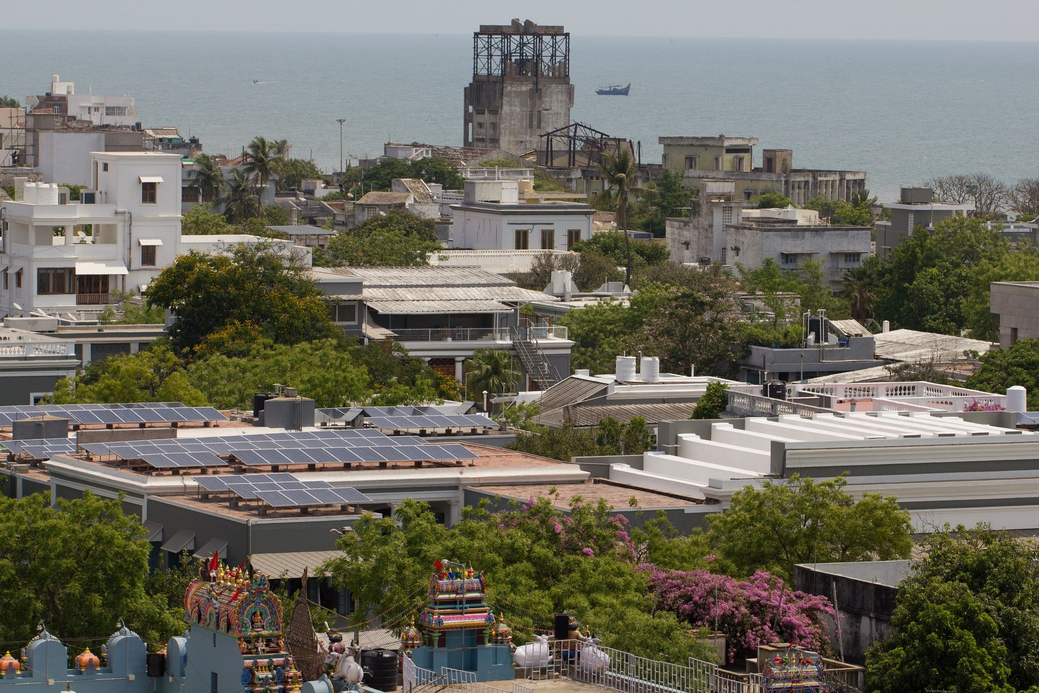 A bird's-eye-view photo of the solar panels installed on SAICE rooftop with the Indian Ocean in the backdrop
