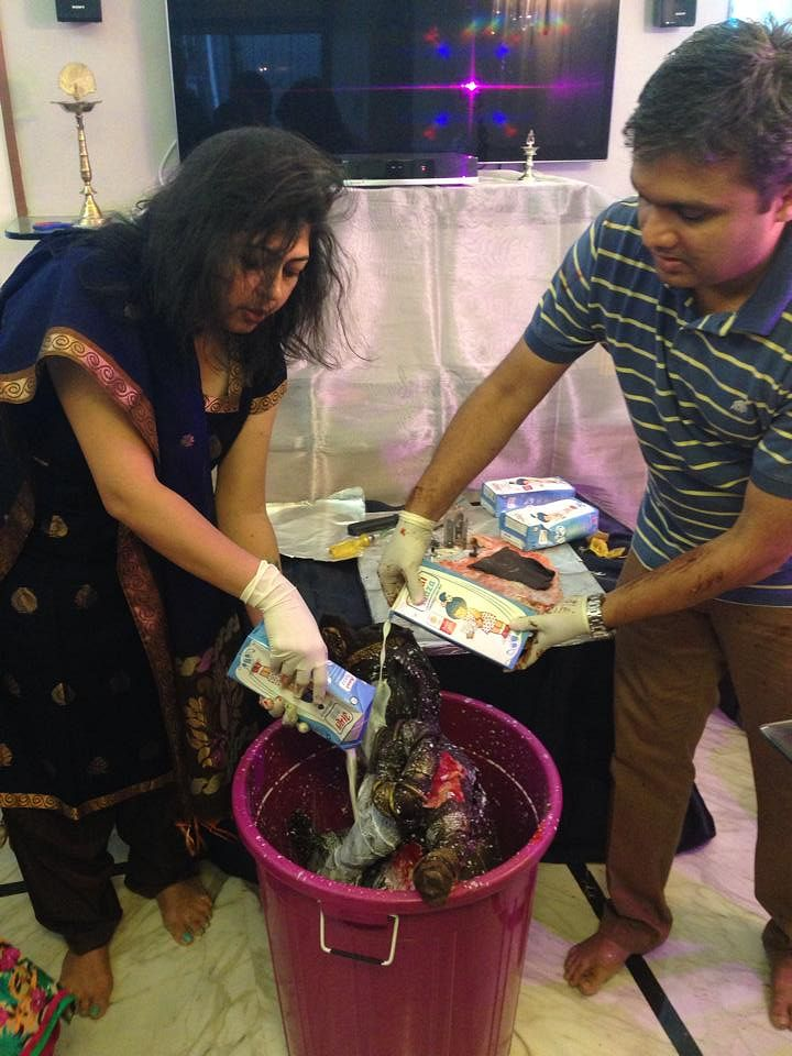 Rintu and her husband immersing the idol into milk