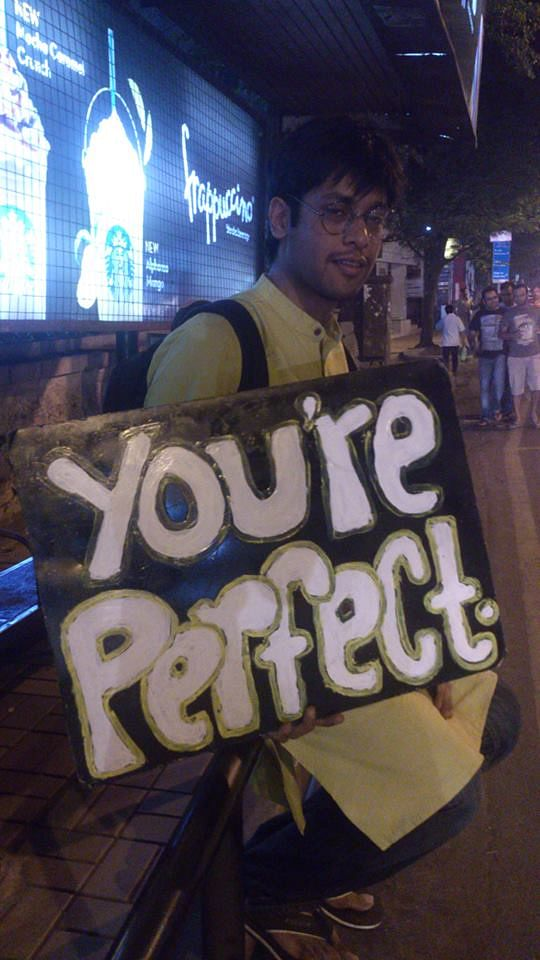 """So Tarun Gidwani let me hold his famous 'You're Perfect' signboard today. While a lot of things disappoint in this city, its people like him & the little things that they do that make the living worthwhile. As I held the board at the bus stop and people passed by, It felt a lot like screening a film to an audience. Some stopped and smiled, some passed by while some thanked me for it. Tarun has even had people who've confessed their personal stories and have shared their moments of joy and hardships alike. Strange how just two words manage to be so simple yet profound at the same time. Thanks Tarun. For being there for everybody,"" says Suyash Kamat."