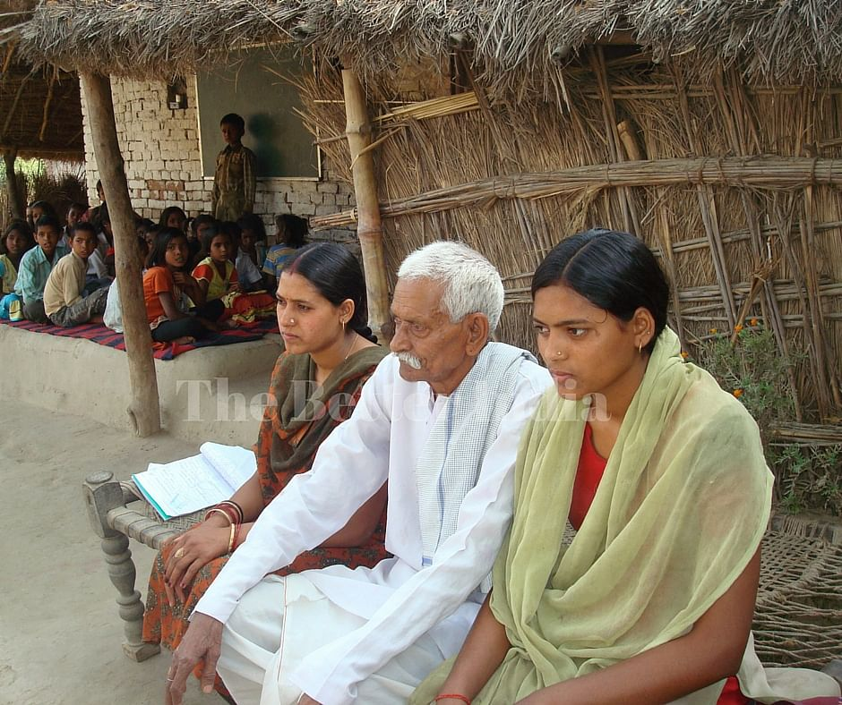 Gudiya, along with her father, Babu Lal Sharma, and sister, Soni, outside the school that is run from the verandah of their home. (Credit: Anjali Singh\WFS)