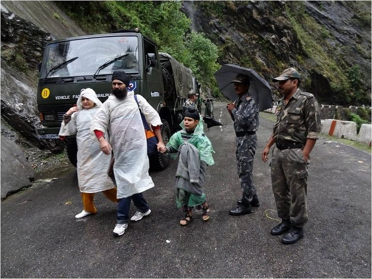 "In this handout photograph released by The Indian Army on June 18, 2013, Indian Army officials escort stranded travellers along a road in Chamoli district in the northern Indian state of Uttarakhand on June 18, 2013. Torrential rains and flash floods washed away homes and roads in north India, leaving at least feared 60 people dead and thousands stranded, as the annual monsoon hit the country earlier than normal, officials said. Authorities called in military helicopters to try to rescue residents and pilgrims cut off by rising rivers and landslides triggered by more than three days of rain in the Himalayan state of Uttarakhand, officials said. -----EDITORS NOTE---- RESTRICTED TO EDITORIAL USE - MANDATORY CREDIT ""AFP PHOTO / INDIAN ARMY"" - NO MARKETING NO ADVERTISING CAMPAIGNS - DISTRIBUTED AS A SERVICE TO CLIENTS"