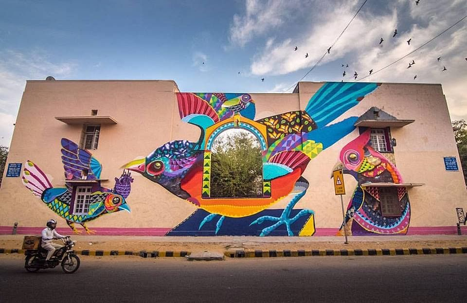 """Colours of the soul by Senkoe. Inspired by the beauty of nature, Senkoe painted these birds in Lodhi colony to represent the colourful diversity of the people who live there and also to encourage them to communicate with each other and share stories, just like the birds would."""