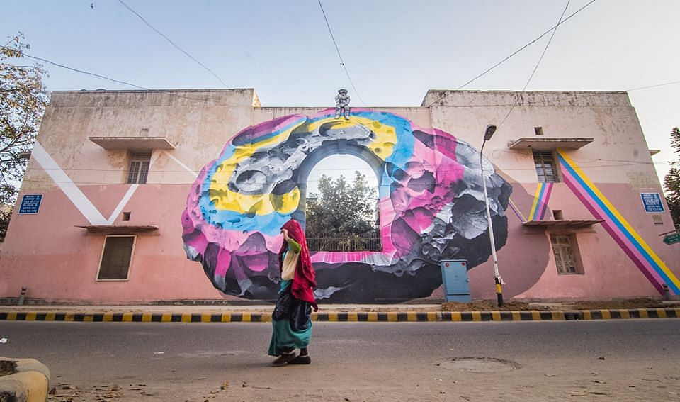 """The astronaut atop the wall is a metaphor for someone who can see things from a different perspective, as a silent viewer of a larger picture. In this case, he is a witness to all the daily activities of Lodhi colony."""