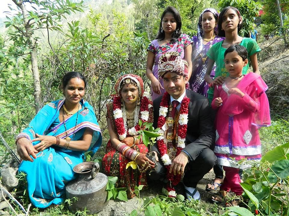 Amidst much fanfare a couple plants a sapling after their marriage ceremony.